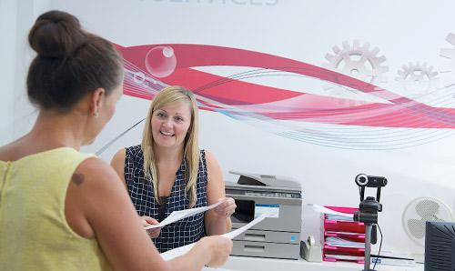 HR officer giving advice to colleague across HR help desk