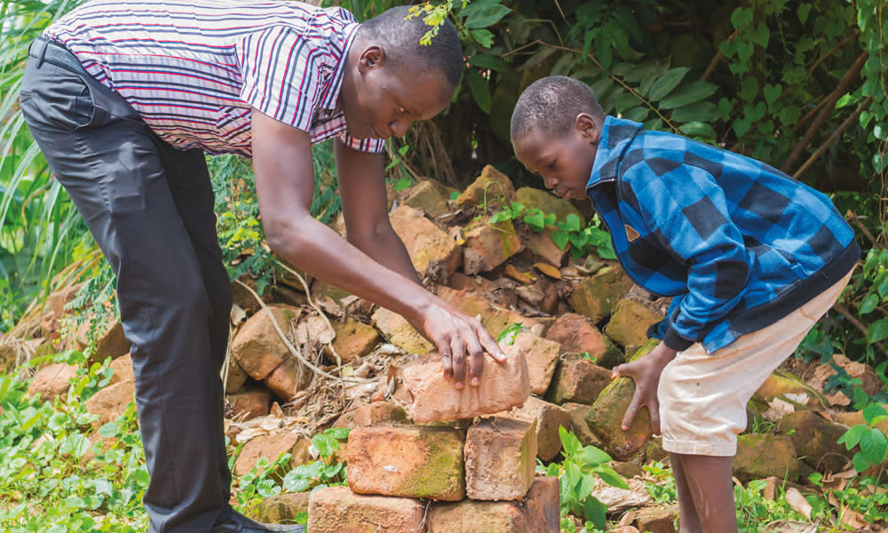 Andrew Amara shows a local child how to build in Nabweru