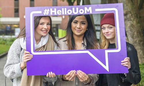 Current students holding Hello UOM sign to welcome new students