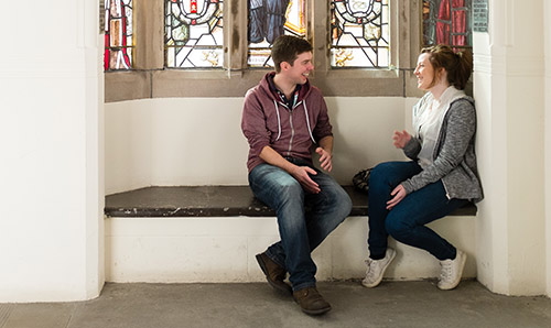 Students sat chatting beneath stained glass window