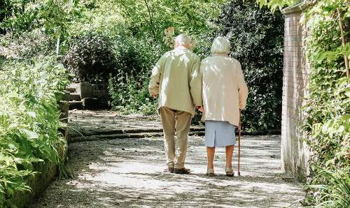 Elderly couple taking a walk through the park. Image courtesy of @micheile on Unsplash