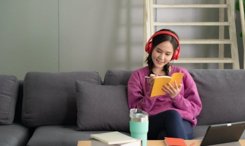 teenager wearing headphones and writing while sitting on sofa