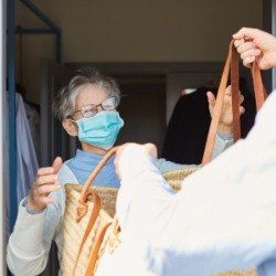 iStock image of shopping being delivered to an older person in a face mask.