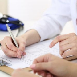 GP and patient completing a form