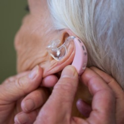 Hearing aid being fitted to an older woman