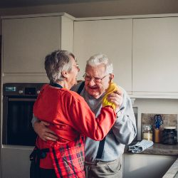 older man and woman dancing in kitchen