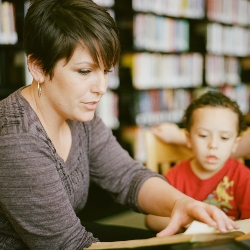 Woman teaching child to read