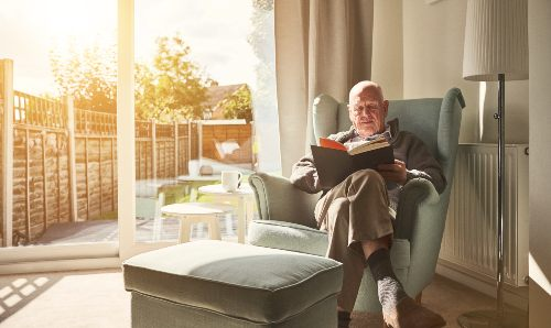 Elderly man reading in armchair
