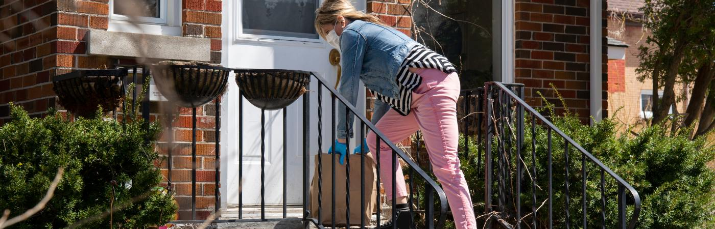 Woman leaving shopping on doorstep