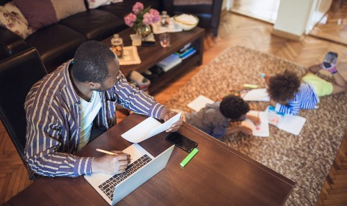 man working at home looking after children