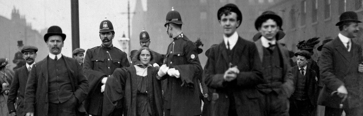 Historical photo of a protester being escorted away by police
