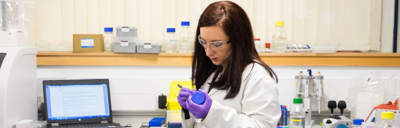 Researcher labelling a bottle