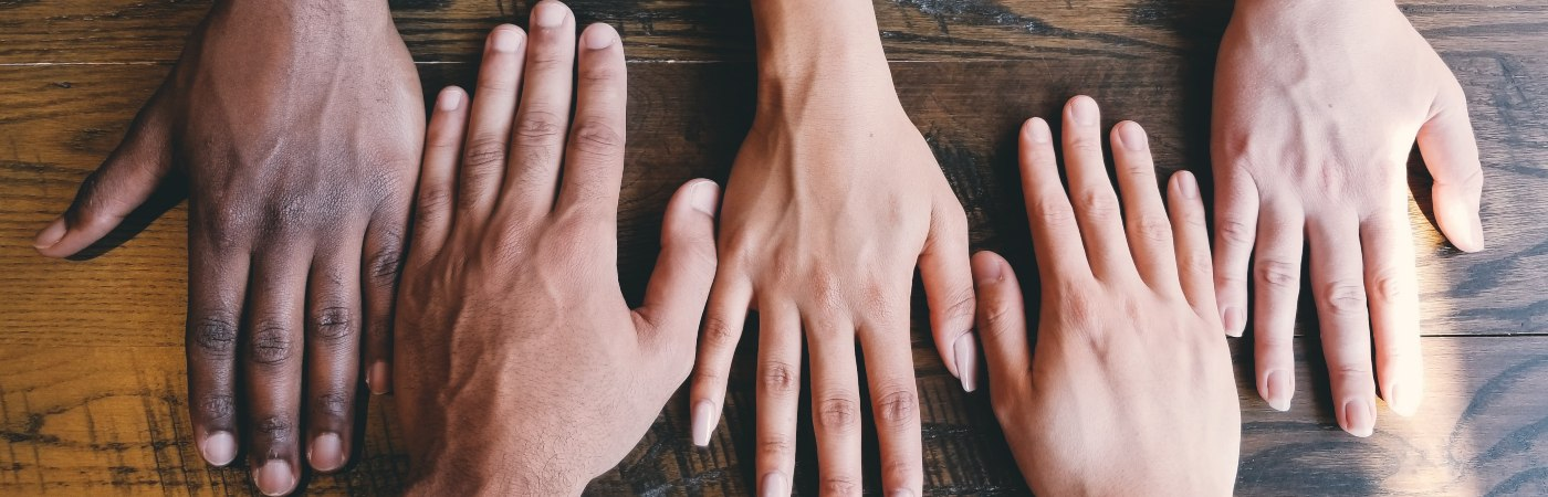 Five different shaped and coloured hands in a line - Photo by Clay Banks on Unsplash