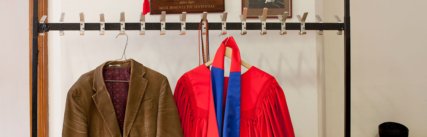 University gown hanging beside jacket
