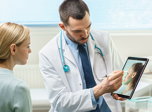 Consultant holding a iPad with patient
