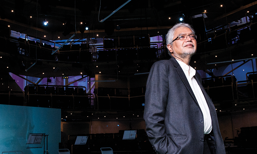 Professor Mukesh Kapila standing in Manchester's Royal Exchange Theatre