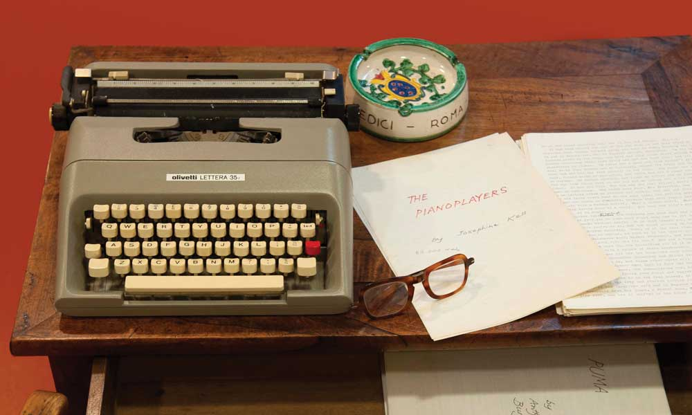 Photo of Anthony Burgess's writing desk, on top of the desk sits a typewriter, pair of glasses, ash-tray and some of his written work