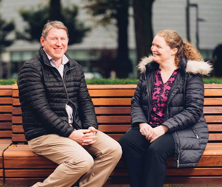 Photo of Dr Philip and Professor Emma Crosbie sat on a bench in Brunswick Park
