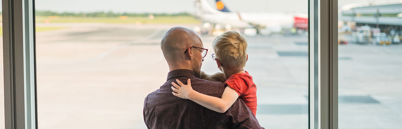 Father and son at an airport watching taxiing aircraft.