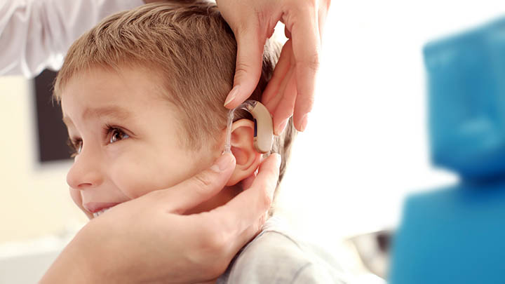 Fitting a hearing aid in a boy's ear.