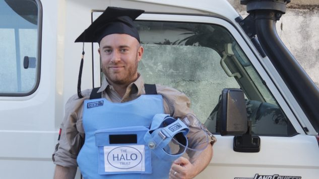 Man stood in front of a HALO Trust branded 4x4 wearing protective equipment and a mortar board.