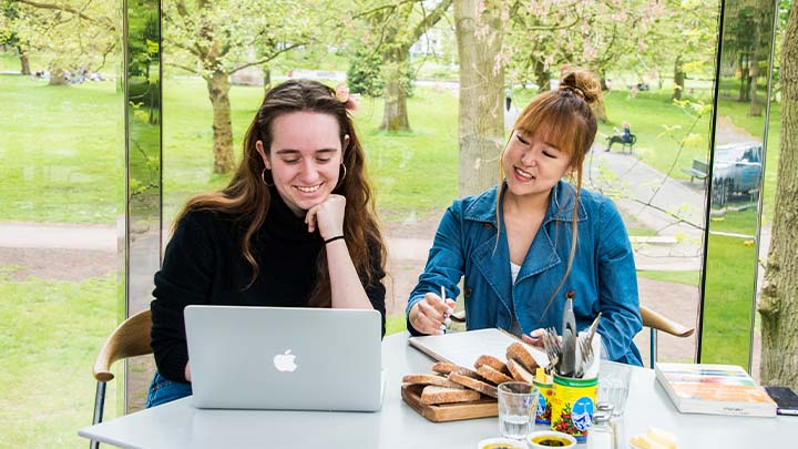 Two smiling female students looking at a laptop