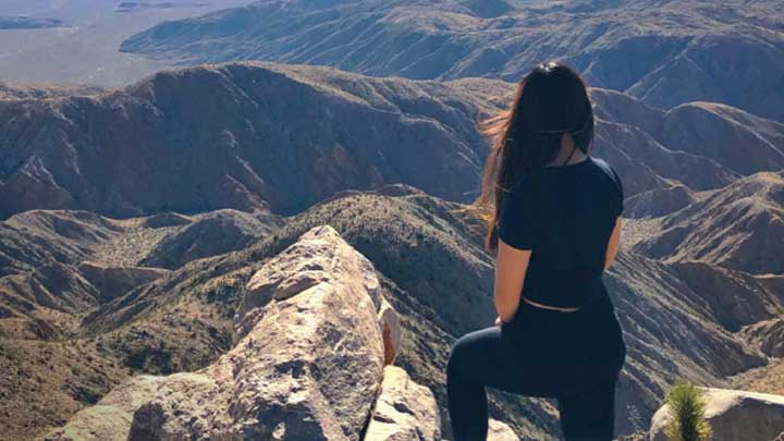 Girl looking down on beautiful mountainous landscape