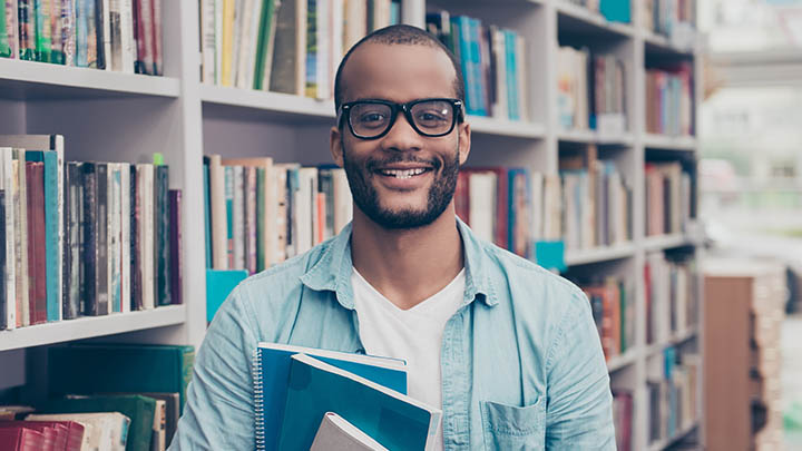 Male student in library smiling at camera