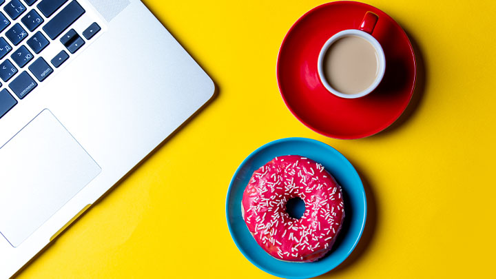 Bright desk with laptop, donut and teacup.
