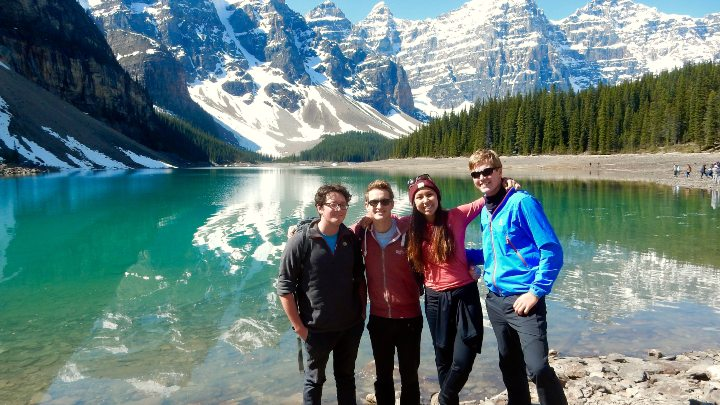 A group of students stood in front of a lake and a mountain