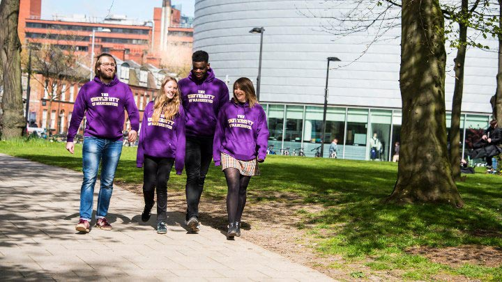 A group of students in purple jumpers walking down Oxford Road