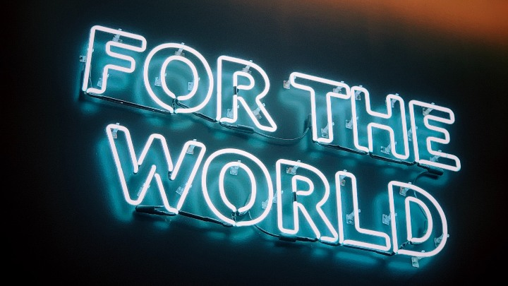 A neon sign reading 'for the world'.
