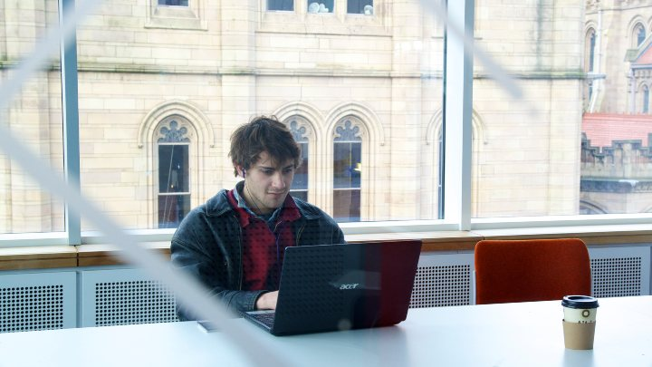 A male student working at a laptop